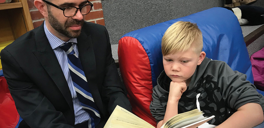 INTRUST employee Devin reads with a young boy at an elementary school