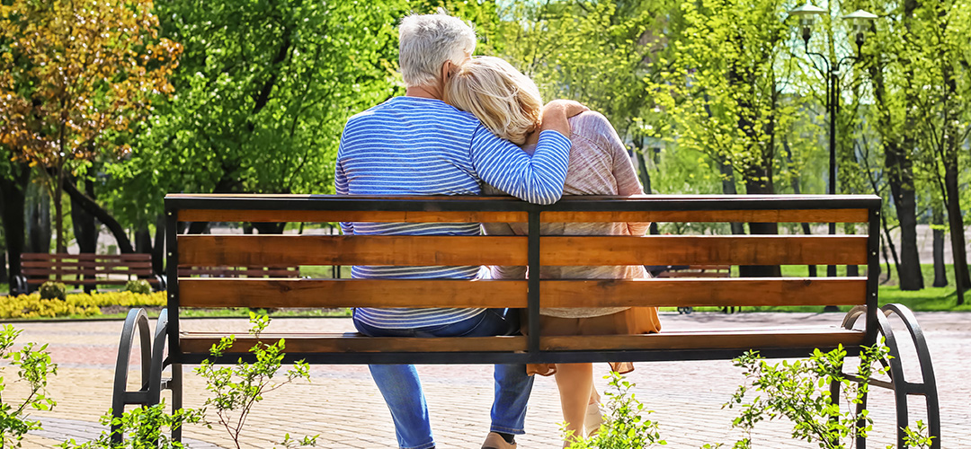 A mature couple sits on a park bench on a sunny day