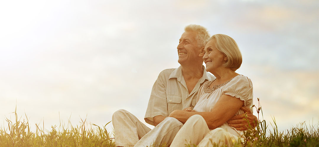 older couple looking out at sunset