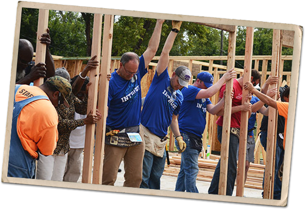 INTRUST Employees helping build a house