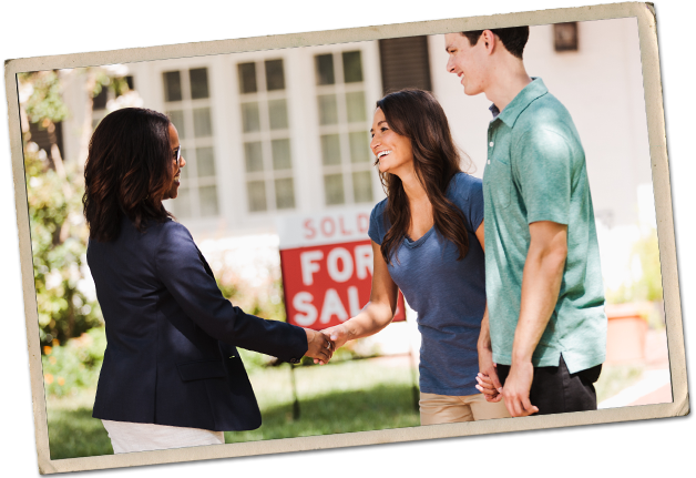A young couple shakes hands with a real estate agent in front of a For Sale sign.