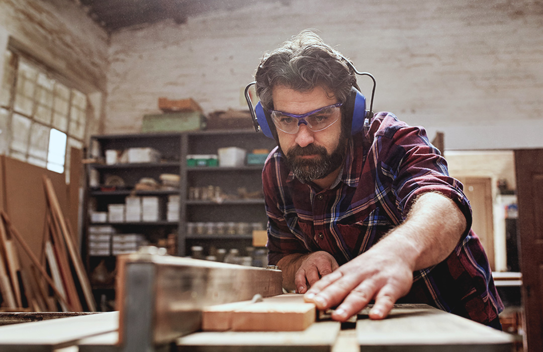 A man works in a woodshop with a saw