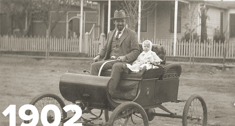 Old image of man in old car with child next to them